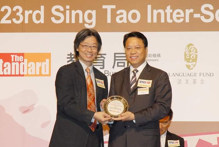 《星島日報》總編輯蕭世和先生頒發紀念品予中原地產港澳行政總裁黃偉雄先生。
