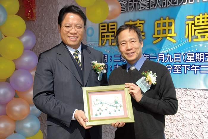 香港心理衛生會總主任(服務)鍾偉成先生(右)向中原地產港澳行政總裁黃偉雄先生致送紀念品。