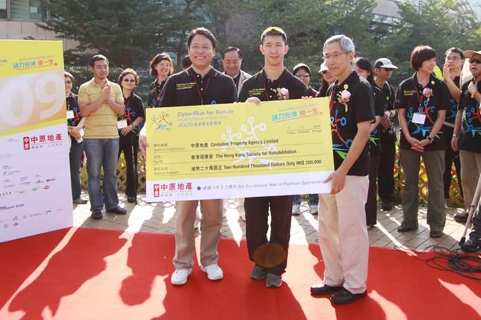 港澳行政總裁黃偉雄(Addy)將二十萬元的善款支票移交予「健康萬步數碼港2009」大使蘇樺偉及香港復康會會