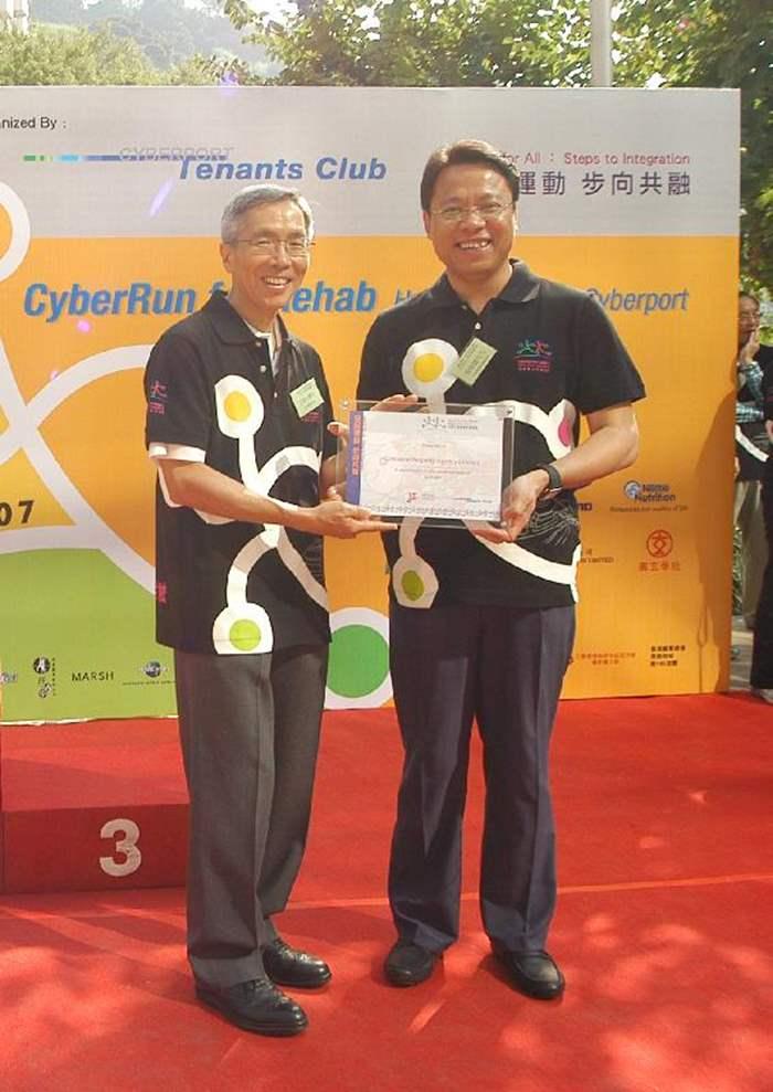 董事總經理黃偉雄從香港復康會會長方津生醫生手中接過紀念座。