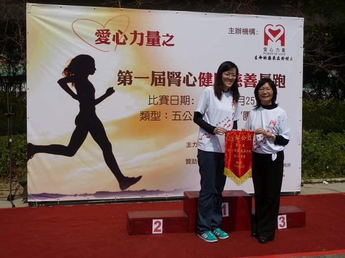 Melody接受愛心力量主席林淑棠小姐頒授錦旗,以示感謝中原地產的贊助及參與。