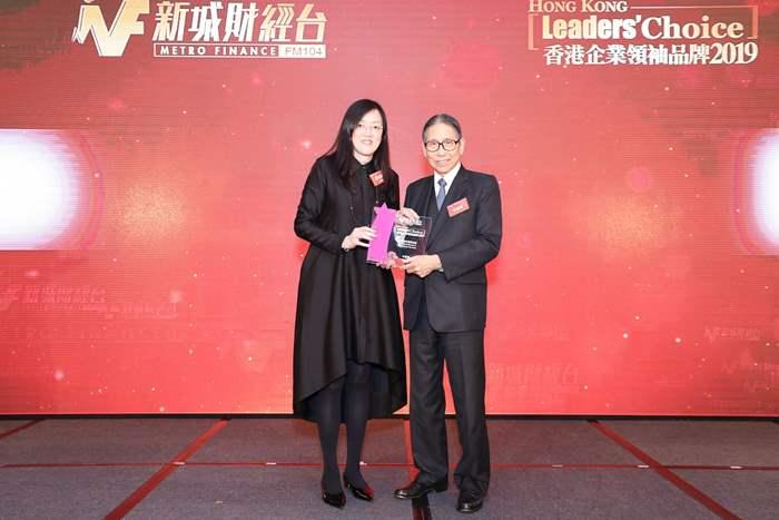 中原薈會所負責人蘇丹莉女士從大會頒獎嘉賓梁智鴻醫生手上接過獎項。